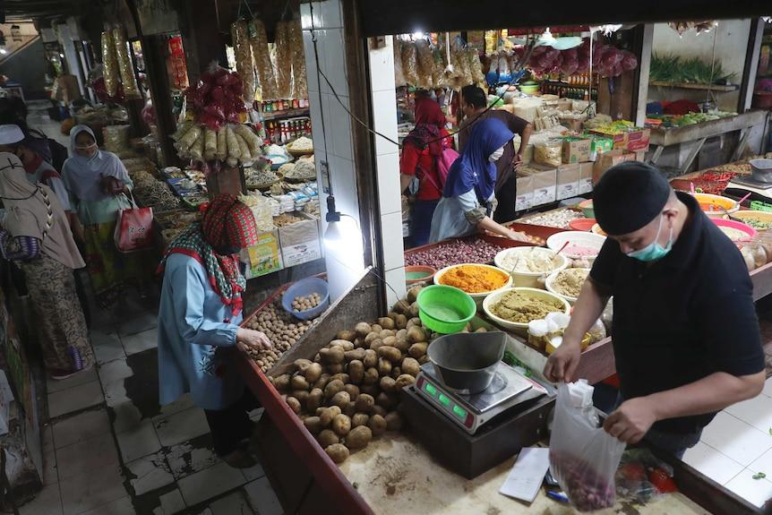 People wear face masks at a market in Jakarta.